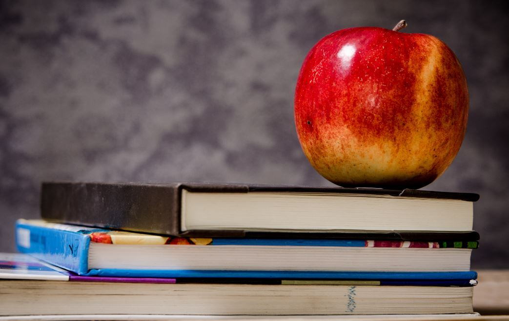 school textbooks with an apple on top and blurry background